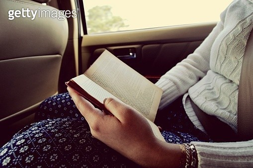 Midsection Of Woman Reading Book While Traveling In Car - gettyimageskorea