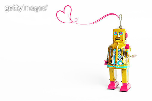 Vintage style toy robot on a white background with pink squiggle heart. - gettyimageskorea
