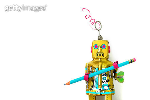 Close up of a vintage style toy robot on a white background holding a blue pencil. - gettyimageskorea