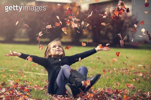 Girl throwing atumn leaves - gettyimageskorea