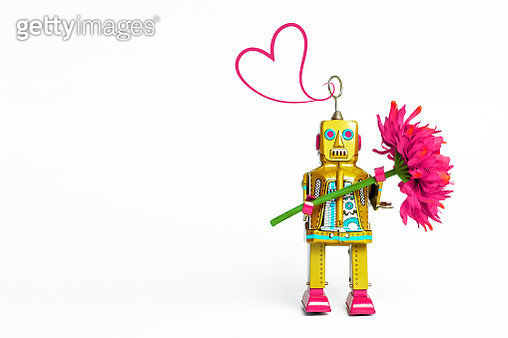 Vintage style toy robot on a white background holding a pink flower with pink heart squiggle. - gettyimageskorea