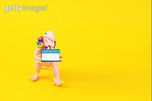 "Pink toy dinosaur wearing a flower collar and holding a ""Hello I'm"" name tag on a yellow background. - gettyimageskorea"
