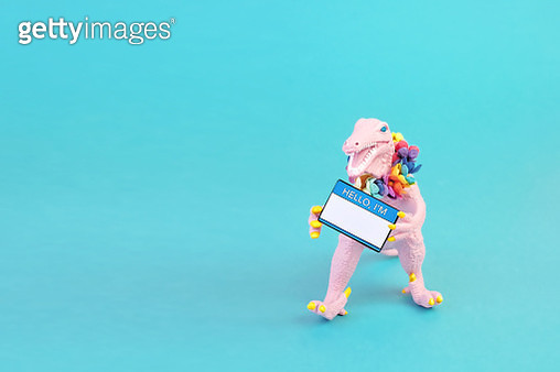 "Pink toy dinosaur wearing a flower collar and holding a ""Hello I'm"" name tag on a teal background. - gettyimageskorea"