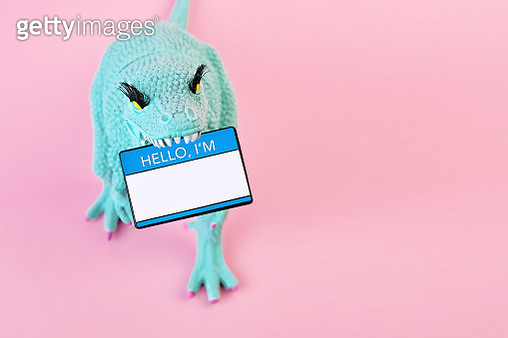 "Close up of a blue toy dinosaur holding a ""Hello I'm"" name tag in its mouth on a pink background. - gettyimageskorea"