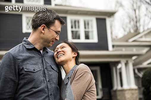 Couple standing in front of home - gettyimageskorea