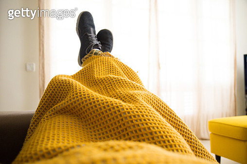 Guy relaxing at home from personal perspective laying in sofa in autumn day covering with blanket while watching television. - gettyimageskorea