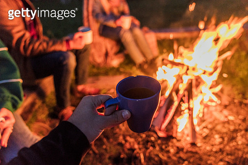 Hand of person holding tea cup, group of people sitting at a camp fire - gettyimageskorea