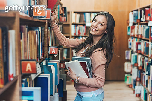 Smiling young woman in a library - gettyimageskorea