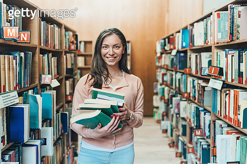 Student holding a stack of books in a library - gettyimageskorea