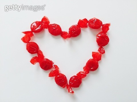 Close-Up Of Candies Arranged In Heart Shape Over White Background - gettyimageskorea