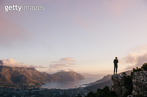Rear View Of Male Hiker Standing On Cliff Against Sky During Sunset - gettyimageskorea