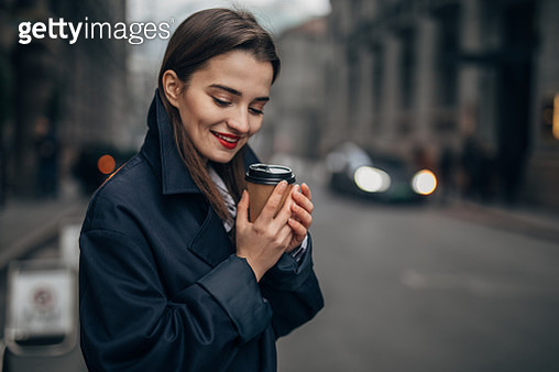One beautiful, young woman with red lipstick and casual clothing is drinking takeaway coffee. - gettyimageskorea