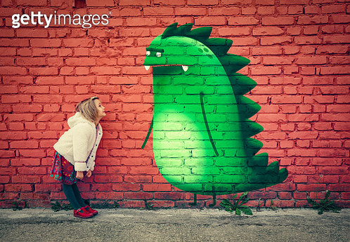 happy young girl smiling to imaginary monster friend painted on outdoor wall - gettyimageskorea