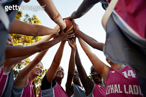 Basket girls standing in a circle, all with hands on the ball - gettyimageskorea
