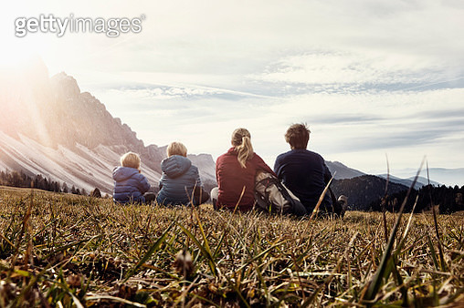 Italy, South Tyrol, Geissler group, family hiking, sitting on meadow - gettyimageskorea