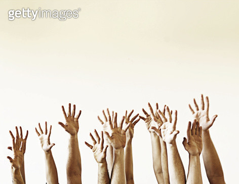 A group of people reaching in the air. - gettyimageskorea