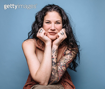 Portrait of dark haired woman on blue background - gettyimageskorea