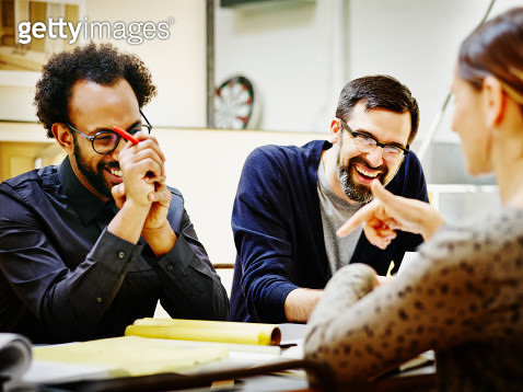 Laughing architects at conference table in office - gettyimageskorea