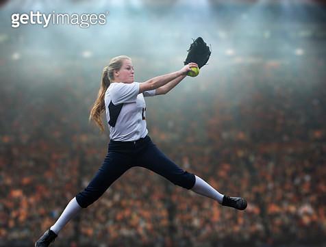 Caucasian softball player pitching ball in stadium - gettyimageskorea