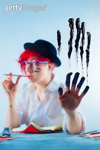 Female writer with fingers stained with ink, creative occupation concept - gettyimageskorea