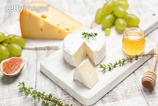 Cheese, Grapes, Honey And Herbs On White Board - gettyimageskorea