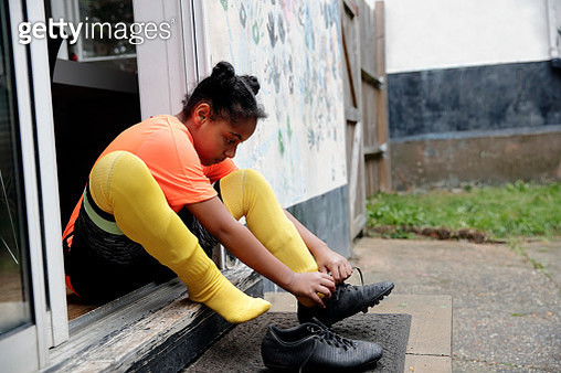 Child sitting on doorstep, doing up her laces, getting ready to play football, preparation - gettyimageskorea