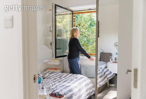 Senior woman standing by bedroom window - gettyimageskorea