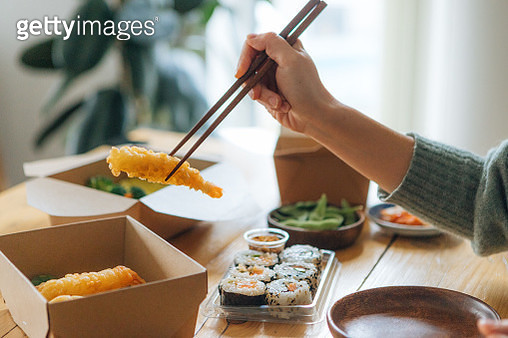 Young Woman Eating Takeaway Asian Meal At Home - gettyimageskorea