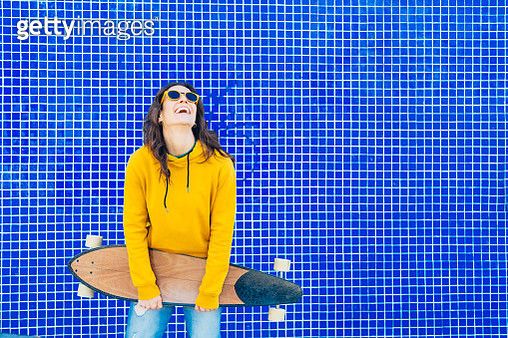 Wearing an yellow sweater walking in the street with a skateboard on her hands and smiling while looking at camera - gettyimageskorea
