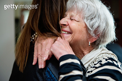 Women of all generations, shape and sizes partying, celebrating life and the birthday of one of them. They are family and friends from 20 to 75 year's old. Here mature grand-daughter hugging grandmother. Horizontal indoors waist up shot. - gettyimageskorea
