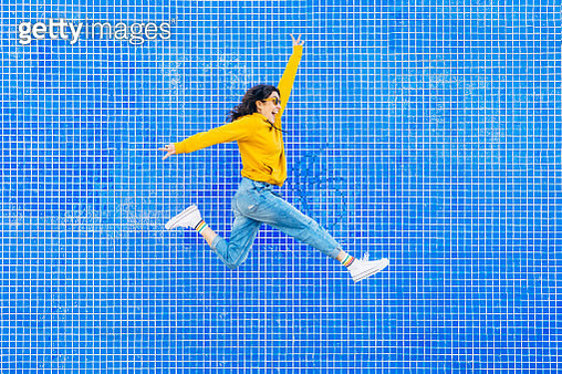 Woman jumping in front of a blue background - gettyimageskorea