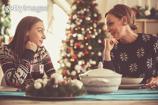 Mother and daughter sitting at the dining table on a Christmas day, about to enjoying all the delicious food, and are having a moment of bonding. - gettyimageskorea