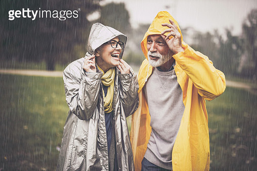 Happy senior couple in raincoats covering their heads during rainy day in nature. - gettyimageskorea
