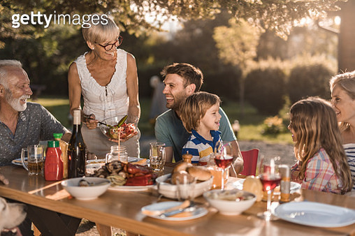 Happy extended family talking while having their lunch in the front yard. - gettyimageskorea