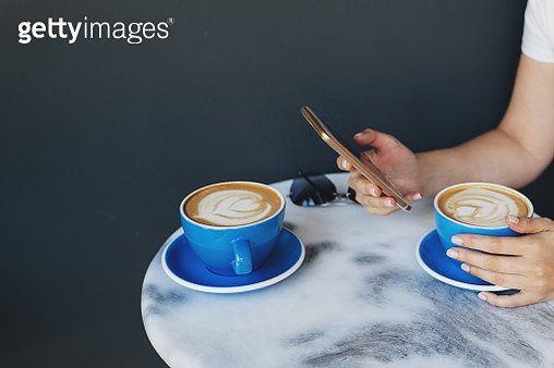female hand using mobile phone with a cup of hot cocoa or chocolate on wooden table, close up - gettyimageskorea
