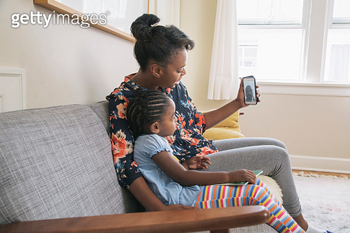 African American mother and daughter video chatting on cell phone - gettyimageskorea