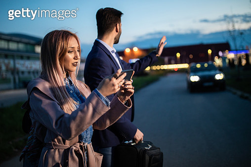 Handsome couple standing on the street with luggage, man waving to taxi , woman using smart phone at night - gettyimageskorea