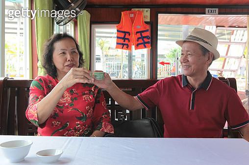 Senior couple making a celebratory toast while cruising. - gettyimageskorea