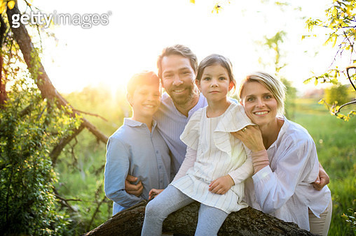 Portrait of family with two children outdoors in spring nature, looking at camera. - gettyimageskorea