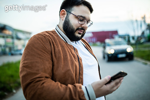 Young, overweight, bearded man  standing on the street on day, using smart phone - gettyimageskorea