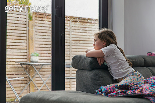 Young girl looking out of window on a rainy day - gettyimageskorea