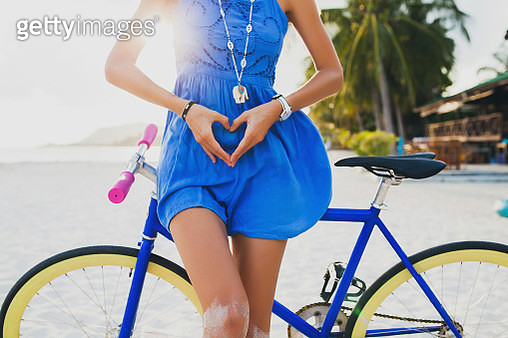 Neck down view of young woman with bicycle making heart shape with hands on sandy beach, Krabi, Thailand - gettyimageskorea
