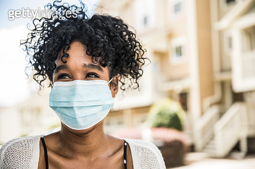 Young woman wearing surgical mask in front of home - gettyimageskorea