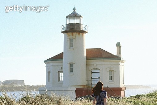 Rear View Of Woman Standing By Lighthouse Against Clear Sky - gettyimageskorea
