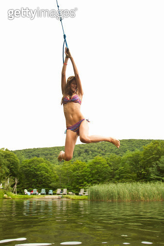 Teenage girl swinging on a rope over a lake - gettyimageskorea