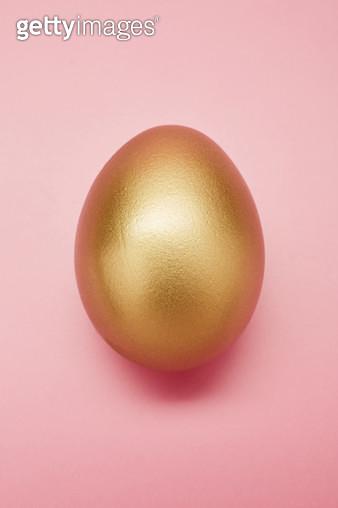 Still life of a golden egg on pink background - gettyimageskorea