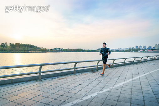 Sporty man with earphones jogging at lake park - gettyimageskorea