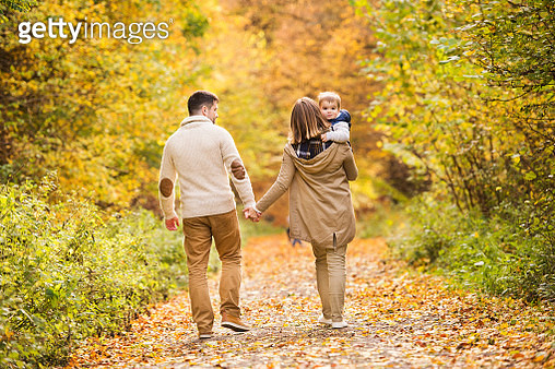 Beautiful young family on a walk in autumn forest. - gettyimageskorea