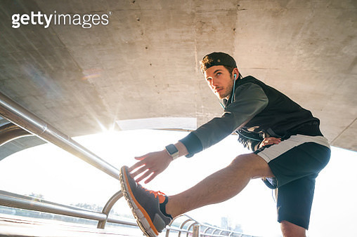 Male runner stretching arms underpass at sunset - gettyimageskorea