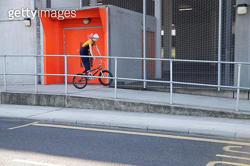 Young woman wearing dungarees doing a wheelie with BMX on ramp by roadside - gettyimageskorea